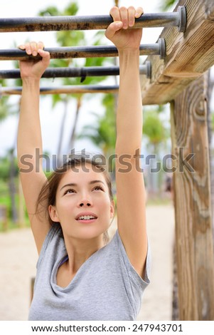 Woman training on fitness brachiation ladder or monkey bars hanging swinging from rung to rung as part of crossfit workout routine. Beautiful Asian girl doing toning exercises exercising arms. - stock photo