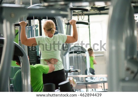 Woman training on horizontal bar trainer in a fitness club, trainer man help for her