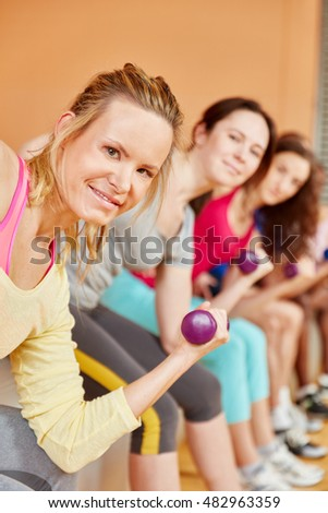 Woman training with weights during pilates class at fitness center