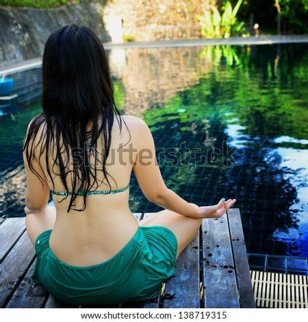 Woman training yoga and meditation at poolside - stock photo