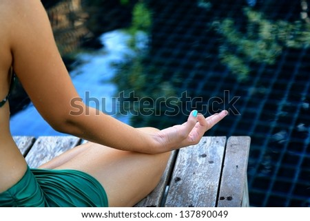 Woman training yoga and meditation at poolside, concentrate on finger - stock photo