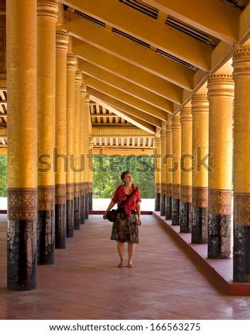 woman traveler between gold columns of Royal Palace in Mandalay, Myanmar(Burma)  - stock photo