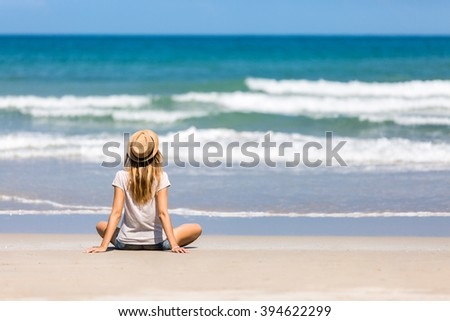 Woman traveler enjoying beautiful sea view, sitting on white sand beach