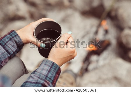 Woman traveler hands holding cup of tea near the fire outdoors. Adventure, travel, tourism and camping concept. Hiker drinking tea from mug at camp. Coffee cooked over a campfire on the nature. - stock photo