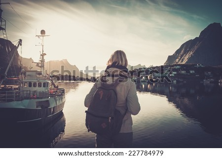 Woman traveler looking at sunset in Reine village, Norway - stock photo
