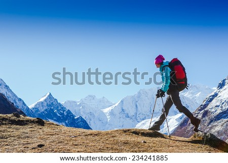 Woman Traveler with Backpack hiking in Mountains with beautiful Himalaya landscape on background mountaineering sport lifestyle concept - stock photo