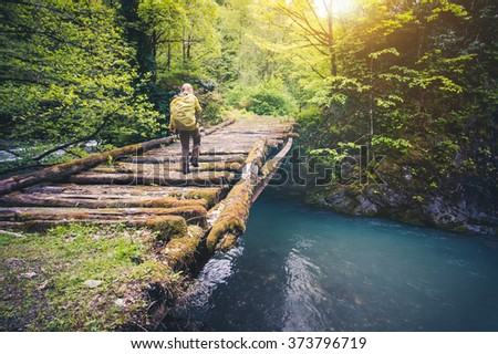 Woman Traveler with backpack hiking on bridge over river Travel Lifestyle concept forest on background Summer journey vacations outdoor - stock photo