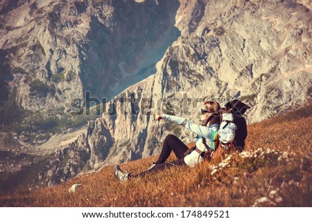 Woman Traveler with Backpack relaxing in Mountains with rocks on background mountaineering hiking sport lifestyle concept - stock photo