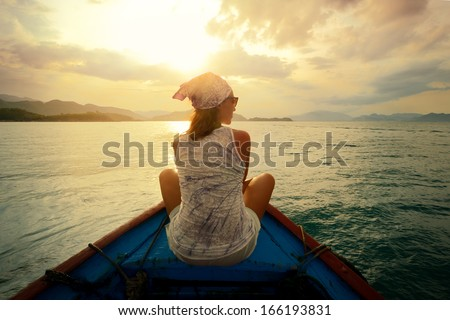 Woman traveling by boat at sunset among the islands. - stock photo