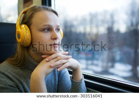Woman traveling by train with favorite music - stock photo