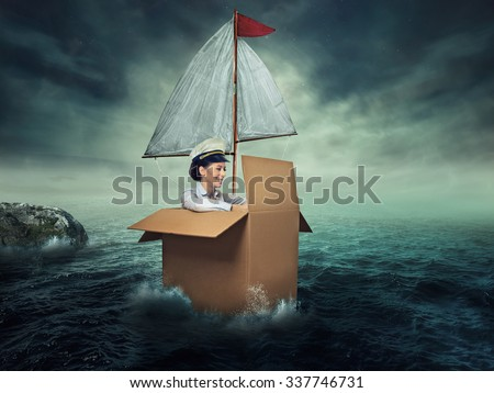 Woman traveling by water. Happiness freedom. Happy smiling young female captain entrepreneur. Designed imaginary vessel made from carton box - stock photo