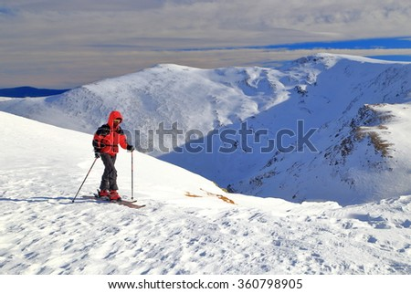 Woman traversing snow covered mountain slope on touring skis