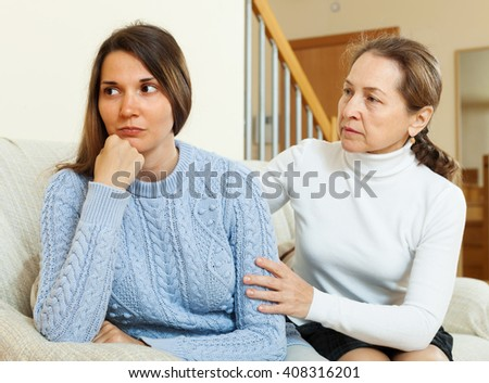 woman tries reconcile with teen daughter after quarrel. Focus on girl - stock photo