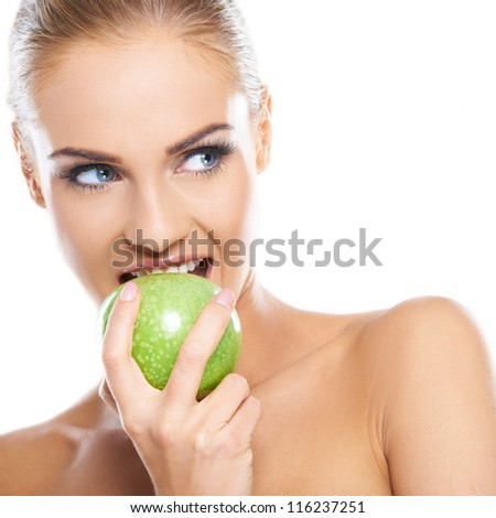 Woman tries to bite a fresh green apple, she is isolated on white - stock photo