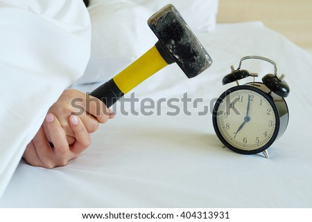 woman tries to break the alarm clock with hammer