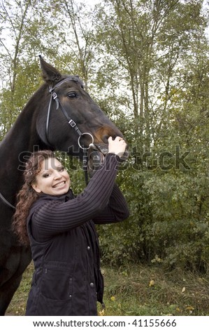 Woman tries to show the horse's teeth. - stock photo