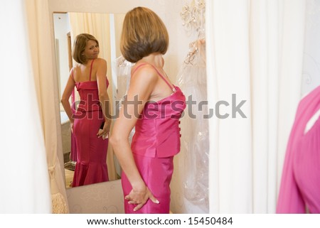 Woman trying on dresses and frowning - stock photo