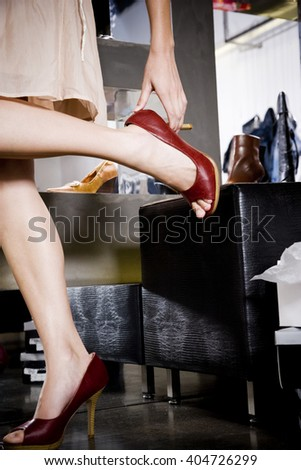 Woman trying on high-heeled shoes in a shoe shop - stock photo
