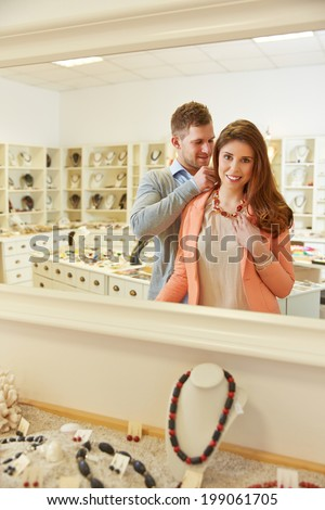 Woman trying on necklace with mirror in a jewelry store - stock photo