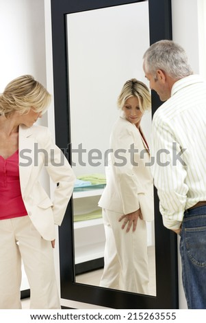 Woman trying on new clothes in fitting room, looking at reflection in mirror, husband watching - stock photo