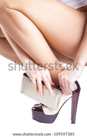 Woman trying on shoes on white background - stock photo