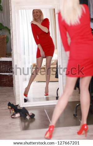 Woman trying red dress shopping for clothing. Beautiful happy smiling young shopper woman looking in mirror standing in clothes store. - stock photo