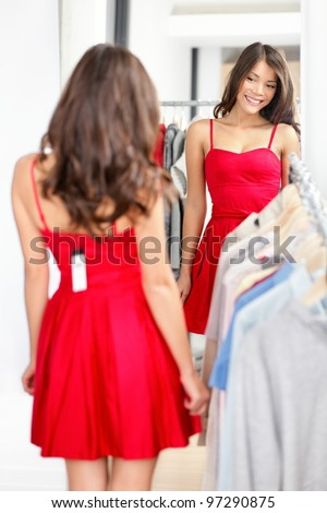 Woman trying red dress shopping for clothing. Beautiful happy smiling young shopper woman looking in mirror standing in clothes store.