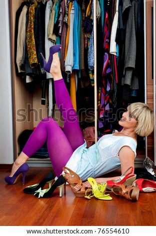 woman trying shoes in front of the closet - stock photo