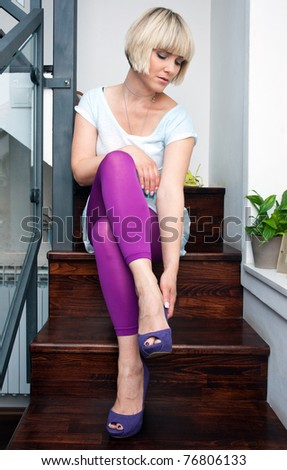 woman trying shoes in her home - stock photo