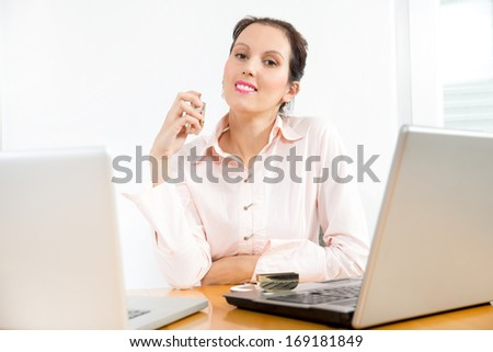 Woman trying the smell of a perfume in the office - stock photo