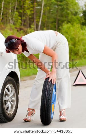Woman trying to change a wheel