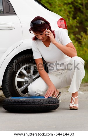Woman trying to change the wheel
