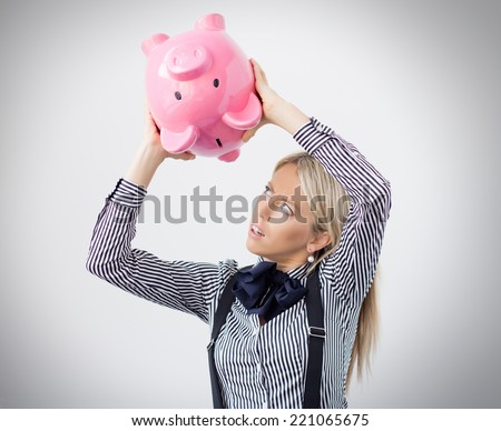 Woman trying to get some money out of piggy bank - stock photo