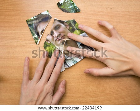 woman trying to glue together picture pieces - stock photo