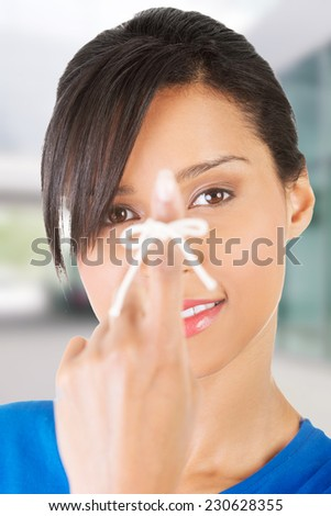 Woman trying to remember by a string on her finger - stock photo