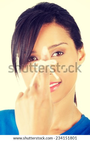 Woman trying to remember what the piece of string round her finger was meant to remind her of, isolated on white background. - stock photo