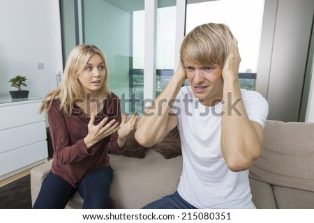 Woman trying to talk as man yells out aloud in living room at home - stock photo
