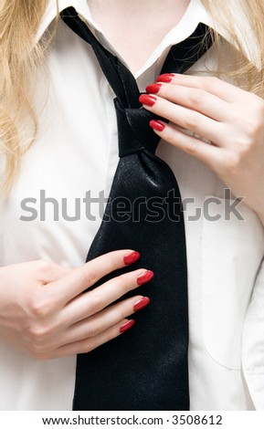 Woman trying to tie her necktie. - stock photo