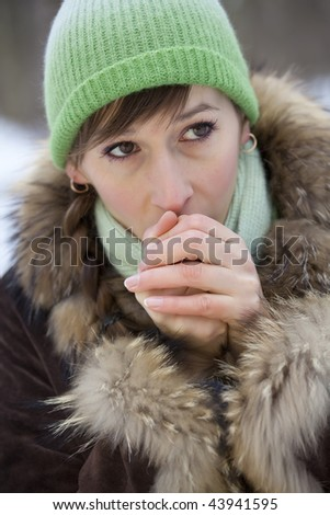woman trying to warm her hands with a breath in winter coat - stock photo