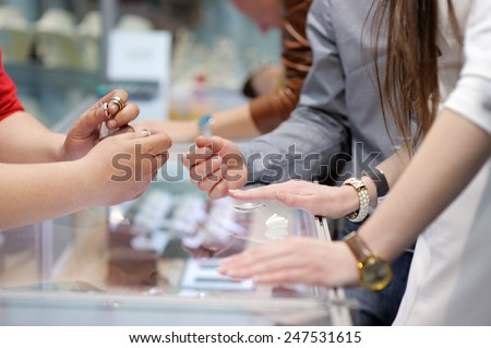 Woman trying wedding rings at a jeweler, focus on ring  - stock photo