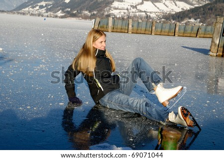 Woman tumble to the ice while skating on frozen lake - stock photo