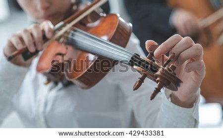 Woman tuning her violing and rotating pegs, cello player on background, selective focus