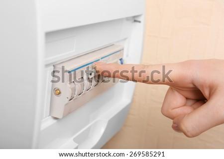 Woman turning off fuse box close up - stock photo