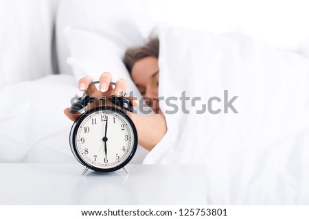 Woman turning off the alarm clock - stock photo