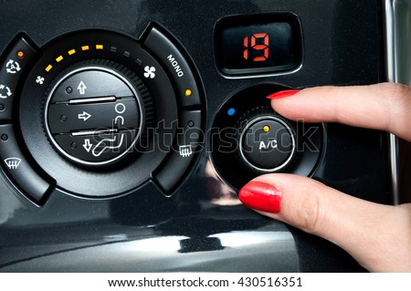 Woman turns on air conditioning in a car - stock photo