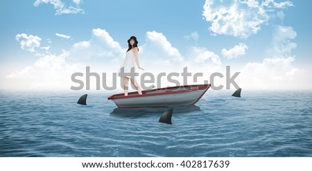 Woman twirling in her pretty dress against sharks circling small boat in the ocean - stock photo