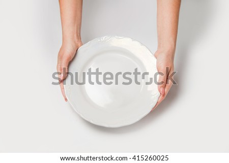 Woman two hands hold a white dish(plate) isolated white - stock photo