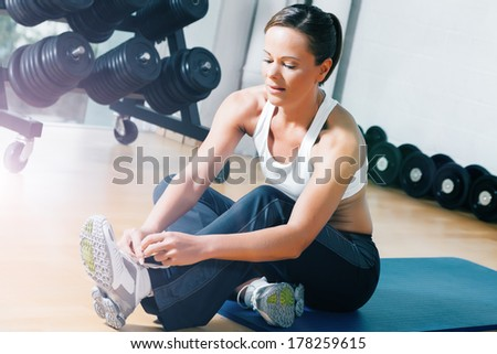 Woman tying her shoelaces before starting her workout in sport gym