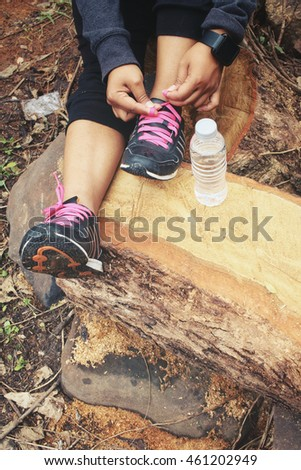 Woman tying running shoe laces with water drink