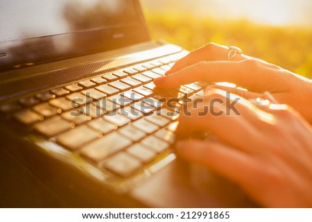 Woman typing on a laptop keyboard in a warm sunny day outdoors. Sunset. Copy Space - stock photo
